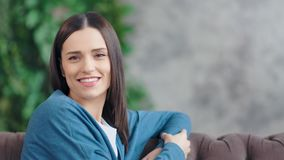 Retrato médio do close-up da jovem mulher de sorriso ocasional que olha a câmera na sala de visitas filme