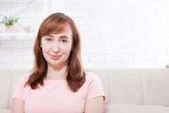 Retrato macro da cara fêmea de sorriso O meio atrativo e bonito envelheceu a mulher que senta-se no sofá e que relaxa em casa men Imagens de Stock Royalty Free