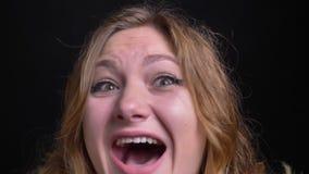 Retrato macro del primer de la hembra caucásica adulta con el pelo corto rubio que es mirada de griterío emocionada y feliz del r metrajes