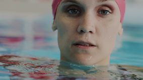 Retrato macro super Mulher profissional nova do nadador no tampão vermelho da nadada para emergir da água na piscina ela filme