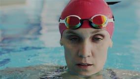 Retrato macro super no movimento lento Cara da mulher profissional nova do nadador no tampão vermelho da nadada para emergir dent filme