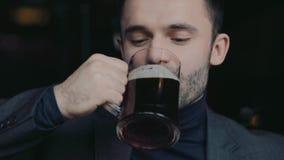 Retrato masculino de un hombre hermoso en un desgaste formal que aumenta una taza de cerveza en una tostada y una consumición cib almacen de video