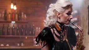 Retrato medio de un jugador de saxofón de sexo femenino rubio en ropa negra de la etapa almacen de metraje de vídeo