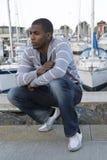Retrato modelo masculino afroamericano atractivo que se pone en cuclillas abajo de a Fotos de archivo libres de regalías