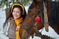 Retrato moreno da mulher com o cavalo no inverno fotografia de stock
