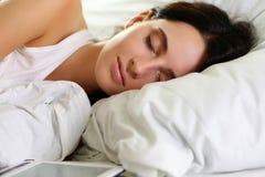 Retrato moreno hermoso joven de la mujer que miente en cama Foto de archivo libre de regalías