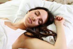 Retrato moreno hermoso joven de la mujer que miente en cama Fotografía de archivo