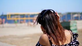 Retrato, muchacha hermosa en los vidrios de sol que llevan los auriculares negros grandes, escuchando la música del smartphone, e almacen de video