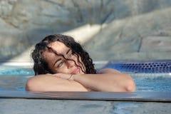 Retrato, mujer madura hermosa en su mejor edad con el pelo rizado oscuro que relaja feliz inclinarse al borde de la piscina imagenes de archivo