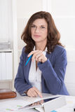 Retrato: Mulher atrativa de meia idade bem sucedida que senta-se no imagens de stock royalty free