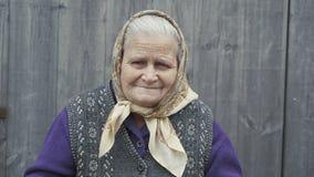 Retrato muy de la vieja mujer sonriente con el cuenco de granos del ` del trigo en las manos 4K almacen de metraje de vídeo