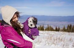 Retrato na mulher bonita na montanha do inverno que abraça seu cão pequeno envolvido em uma cobertura Fotografia de Stock