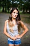 Retrato no parque de uma menina adolescente bronzeada bonita do estudante fotografia de stock