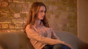 Retrato no perfil do estudante fêmea novo concentrado que senta-se no sofá e na tevê de observação na atmosfera de casa acolhedor filme