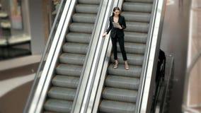 Retrato novo da mulher de negócios que fala no telefone em escadas rolantes Comprimento completo da mulher de negócio no shopping Foto de Stock Royalty Free