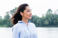 Retrato oblicuo del primer de la mujer morena asiática hermosa que lleva la camisa azul en fondo de la naturaleza fotos de archivo libres de regalías
