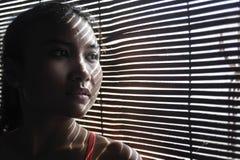 Retrato obscuro da mulher asiática bonita nova nos panos do esporte do gym que olham através das venezianas foto de stock