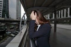 Retrato oscuro de la cabeza conmovedora asiática joven frustrada subrayada de la mujer de negocios con las manos y de la sensació foto de archivo libre de regalías