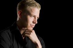 Retrato oscuro del hombre atractivo joven que mira a un lado. Imagen de archivo