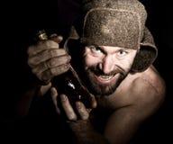 Retrato oscuro del hombre barbudo siniestro malvado asustadizo con sonrisa boba, sosteniendo una botella de coñac hombre ruso ext Fotos de archivo libres de regalías
