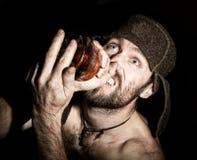 Retrato oscuro del hombre barbudo siniestro malvado asustadizo con sonrisa boba, sosteniendo una botella de coñac hombre ruso ext Fotografía de archivo libre de regalías