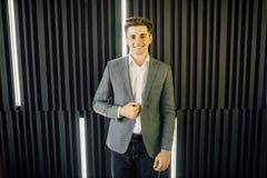 Retrato otimista de um homem de negócios novo considerável que está contra a parede de madeira escura Imagem de Stock Royalty Free