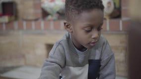 Retrato pequeño de jugar enfocado del niño muchacho afroamericano y del divertirse con los juguetes en sala de estar almacen de video