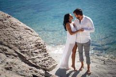 Retrato perfecto de los pares, colocándose en la playa de piedra detrás del mar Mediterráneo, luna de miel en Grecia imagenes de archivo