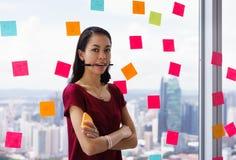 Retrato Person With Many Sticky Notes ocupado en ventana de la oficina imagen de archivo