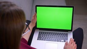 Retrato posterior de la empresaria en vidrios que mira en el ordenador port?til atento con la pantalla verde de la croma en casa metrajes