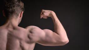 Retrato posterior del primer del hombre caucásico joven que muestra su bíceps muscular y que demuestra cómo fuerte está en negro metrajes