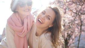 Retrato próximo de duas mulheres, novo e maduro Selfie no fundo do sol brilhante da mola e da florescência cor-de-rosa vídeos de arquivo
