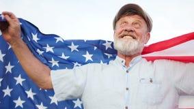 Retrato próximo de um homem idoso com uma bandeira dos EUA O pensionista olha acima e sorri Fundo do grunge da independ?ncia Day video estoque