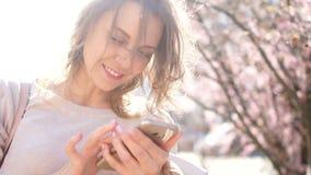 Retrato próximo de uma jovem mulher com um smartphone em suas mãos A menina sorri folheando através da foto em seu telefone filme