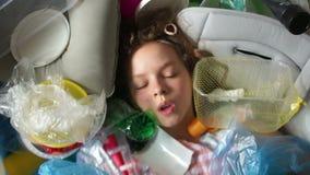 Retrato próximo de uma menina em uma pilha do lixo plástico A criança abre seus olhos amedrontados e respira duramente Salvar video estoque