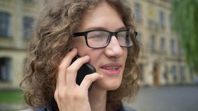 Retrato próximo do homem considerável novo nos vidros com cabelo encaracolado longo que fala no telefone celular e que sorri, est vídeos de arquivo