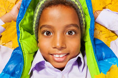 Retrato próximo do menino preto nas folhas de outono Imagens de Stock