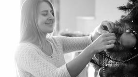 Retrato preto e branco da jovem mulher de sorriso que decora a árvore de Natal imagens de stock royalty free