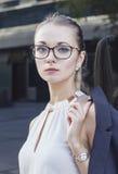 Retrato preto e branco da jovem mulher séria com vidros Fotografia de Stock Royalty Free