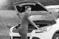 Retrato preto e branco da mulher que está em carro quebrado com op Imagem de Stock