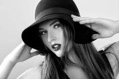 Retrato preto e branco da mulher 'sexy' bonita no chapéu negro imagem de stock royalty free