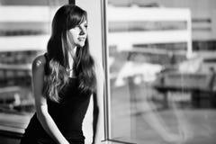 Retrato preto e branco de uma partida de espera da mulher no aeroporto fotografia de stock royalty free