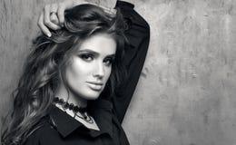 Retrato preto e branco do close up da mulher bonita nova na camisa preta que levanta na frente de uma parede do metal Imagens de Stock