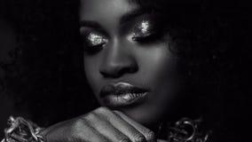 Retrato preto e branco surreal do close-up do modelo fêmea afro-americano novo com composição lustrosa do ouro Cara Art Fotografia de Stock