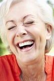 Retrato principal e dos ombros de rir a mulher superior foto de stock royalty free
