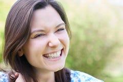 Retrato principal y de los hombros al aire libre de reír a la mujer joven imagen de archivo libre de regalías