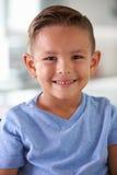 Retrato principal y de los hombros del muchacho hispánico sonriente en casa Foto de archivo
