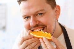 Retrato profissional de Bite Orange Slice do cozinheiro chefe imagens de stock