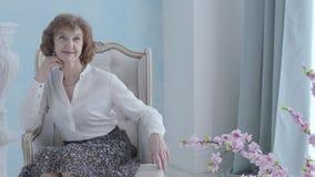 Retrato que encanta a la mujer madura elegante en la blusa blanca que se sienta en la sonrisa de la butaca La situación irreconoc almacen de video