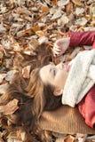 Retrato que miente en las hojas, visión superior de la mujer joven Imágenes de archivo libres de regalías